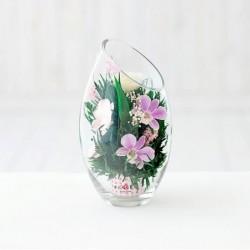 Розовато-белые и фиолетовые орхидеи с айвори розами в средней овальной вазе со скошенным верхом
